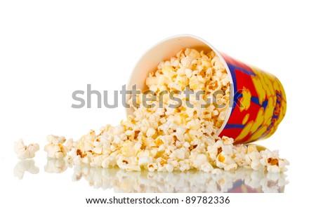 Full bucket of popcorn dropped isolated on white - stock photo