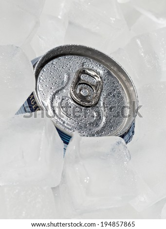 Full can beer or soda with drops of condensation. Ice cubes around the can. - stock photo