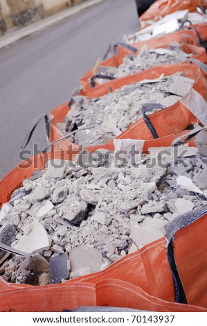 Full construction waste bags in a row - stock photo