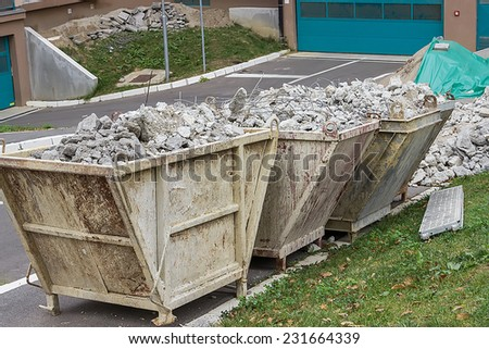 Full container of concrete debris. Trash containers full of concrete debris. - stock photo