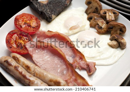 Full cooked English breakfast with a serving of fried eggs, bacon, tomato, sausages, hash brown and mushrooms, close up view on a plate - stock photo