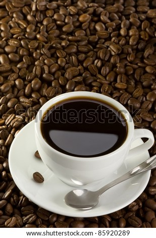 full cup of coffee at roasted beans - stock photo