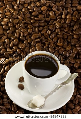 full cup of coffee at roasted beans background - stock photo