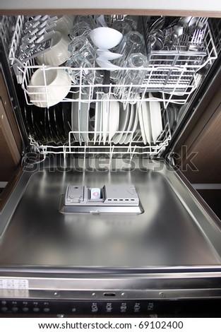 full dishwasher, focus on dishwasher detergent tablet - stock photo