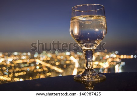 Full drink glass in front of city skyline bokeh - stock photo