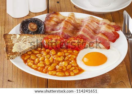 Full English breakfast on an old pine kitchen table. - stock photo