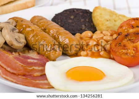 Full English Breakfast - Traditional English fry-up with egg, bacon, mushrooms, tomatoes, sausages, black pudding, hash browns and baked beans. Served with slices of toast. - stock photo