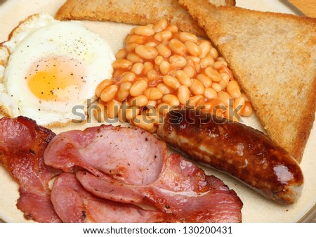 Full English breakfast with bacon, sausage, egg, baked beans and fried bread. - stock photo