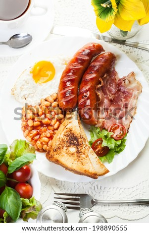 Full English breakfast with bacon, sausage, fried egg, baked beans and tea - stock photo