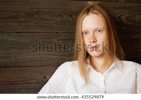 Full face beautiful portrait of beautiful and young Caucasian girl on wooden background. Blond office woman in white shirt staring attentively at camera with relaxed face and peaceful emotions. - stock photo
