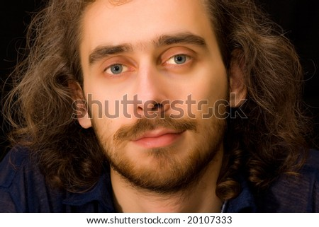 Full face portrait of young adult brown-haired man, dark background, untidy curly hair
