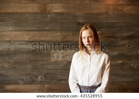 Full face portrait of young office worker on wooden background. Attractive Caucasian woman with blue eyes, ivory skin and blond hair looking at camera with natural beauty and incredible simplicity. - stock photo