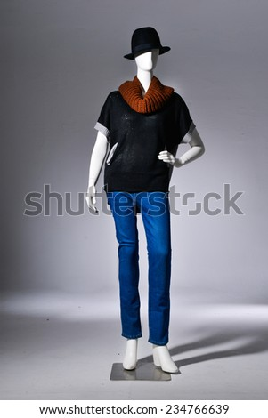 Full female red clothing in jeans with black hat on mannequin on light background - stock photo