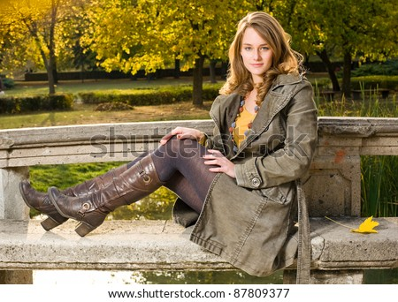 Full figure portrait of beautiful young woman in the park at fall. - stock photo