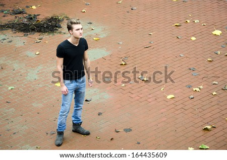 Full figure shot of attractive young man alone in large empty space with fallen leaves - stock photo