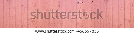Full frame, large and wide shot of an old, weathered, light pastel red, pink wooden wall. - stock photo