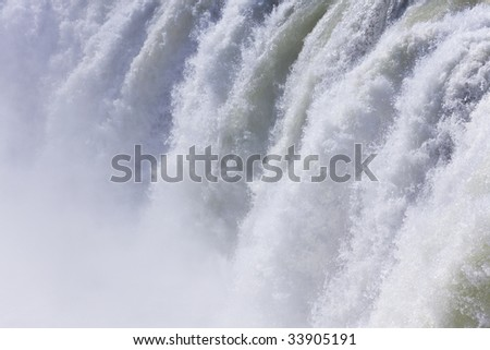 Full frame shot of water cascading over a huge waterfall. Shot on location at Godafoss in Iceland. - stock photo