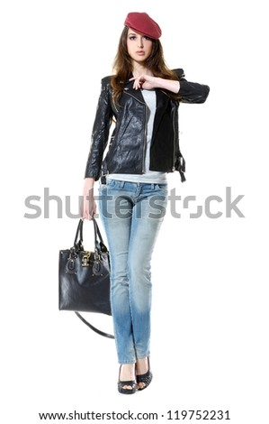 Full-frame young woman wearing sunglasses in cap with handbag posing in studio - stock photo