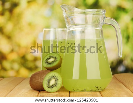 Full glass and jug of kiwi juice and kiwi on wooden table outdoor - stock photo