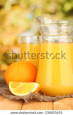 Full glass and jug of orange juice and oranges on wooden table outdoor - stock photo