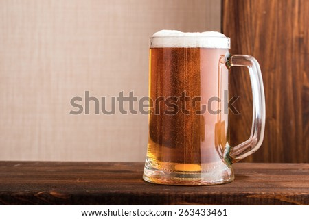 full glass of beer on a wooden table top