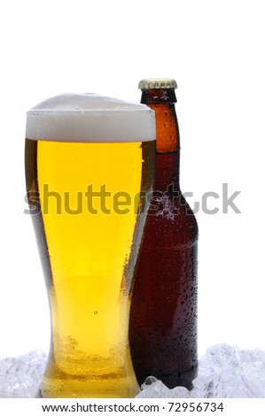 Full glass of cold beer in front of a brown beer bottle. Both objects are covered with condensation and standing in a bed of ice. Vertical format over a white background. - stock photo