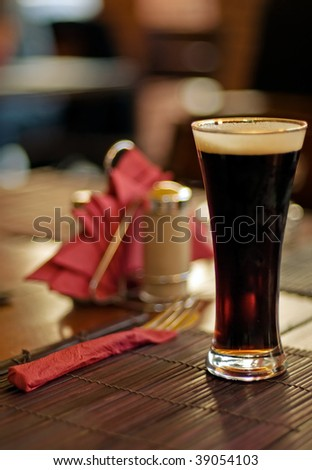 Full glass of dark beer at the wood cafe table - stock photo