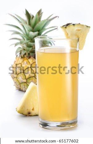 Full glass of fresh pineapple juice and pineapple fruit on the back. - stock photo