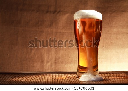 Full glass of freshness beer with foam on table against gray canvas background