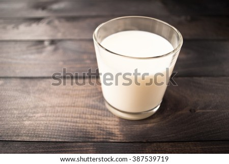 Full glass of milk on brown rustic wooden background - stock photo