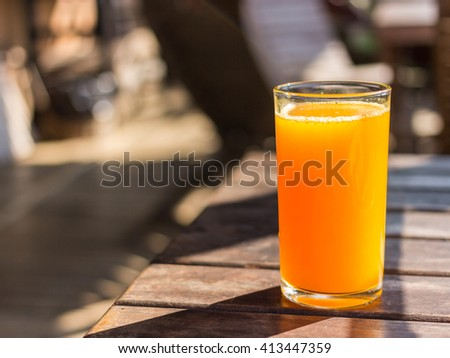 Full glass of orange juice close-up. Fresh orange juice on wooden table in out of focus unidentified restaurant in the morning in summer - stock photo