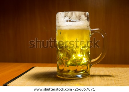 Full glass tankard of glowing golden refreshing draft, lager or beer standing on a wooden counter in a pub, tavern or bar for a relaxing lunch or evening entertainment - stock photo