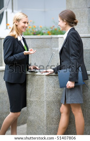 Full-growth portrait of two businesswomen discussing at a meeting in  front of the office building - stock photo