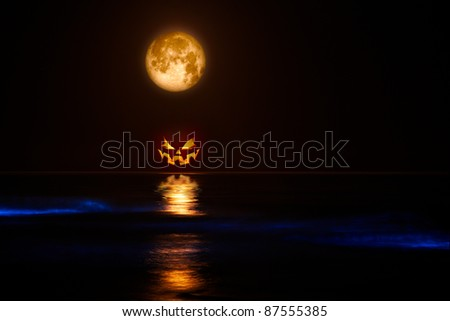 Full Harvest Moon and Jack-o-Lantern & Sea Glowing with Sinister Bio-luminescence Waves - stock photo