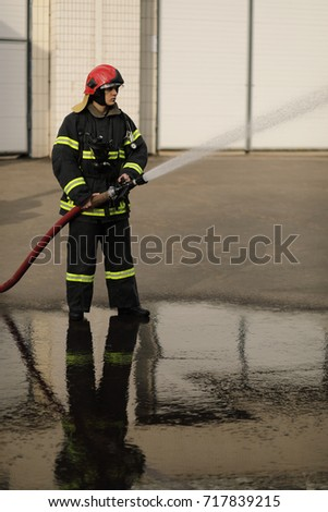 full-height portrait of fireman holds and adjust nozzle and fire hose spraying high pressure water