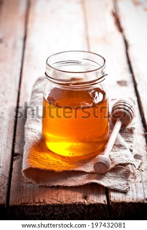 full honey pot and honey stick on rustic wooden board - stock photo