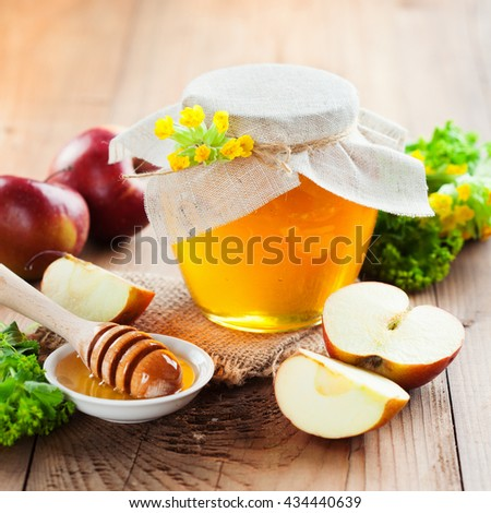 Full honey pot and honey stick with fresh flowers and ripe apples on rustic wooden background, selective focus. Autumn time - stock photo