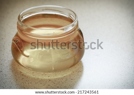 full honey pot glass, jar of organic floral honey or syrup on table