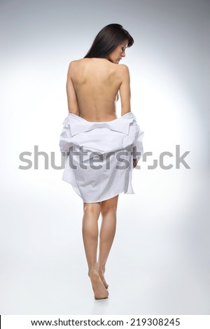 full image of beautifull woman in shirt on white background. back view of dark-haired naked girl looking down - stock photo