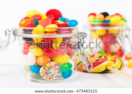 Full jar of colorful candy closeup on white background