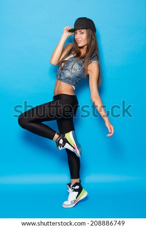 full lenght Portrait of pretty young woman in casual wear against blue background - stock photo