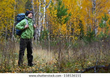 Full lenght portrait of the mature backpacker in an autumn forest - stock photo