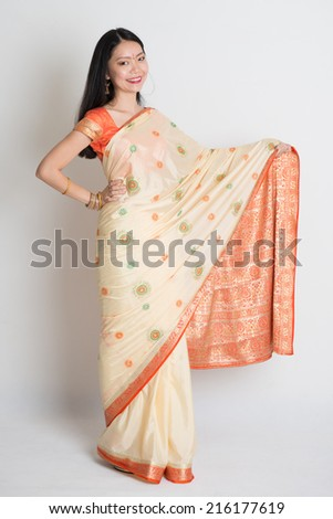 Full length Asian Indian girl smiling and hand showing something on plain background. - stock photo