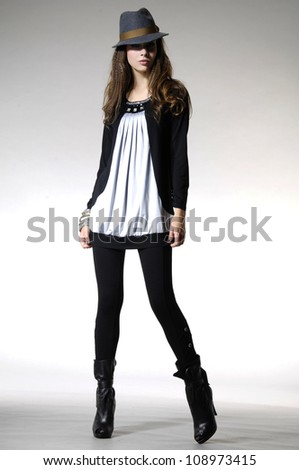 Full length attractive young fashion model in hat posing in light background - stock photo