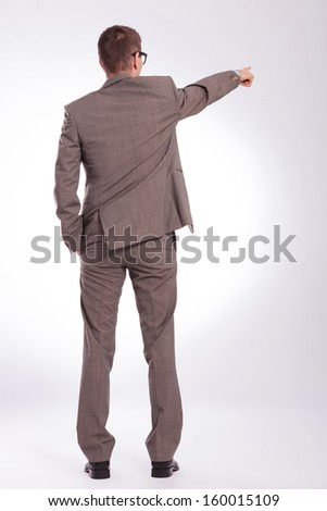 full length back view picture of a young business man pointing forward while holding a hand in his pocket. on a gray background