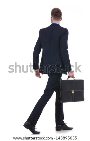 full length back view picture of a young business man with a suitcase in his hand walking away. on white background - stock photo