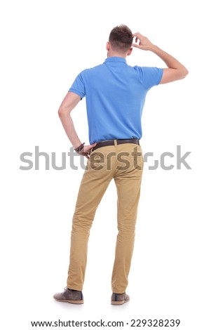 full length back view picture of a young casual man thinking while holding a hand on his waist and scratching his head with the other. isolated on a white background - stock photo