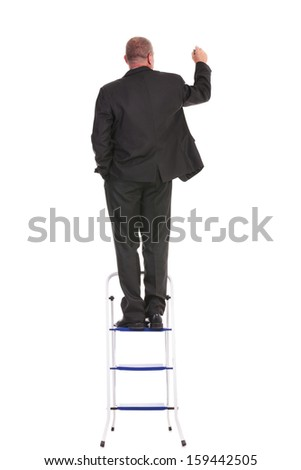 full length back view portrait of a business man standing on a ladder and writing on an imaginary screen while holding a hand in his pocket. on a white background - stock photo