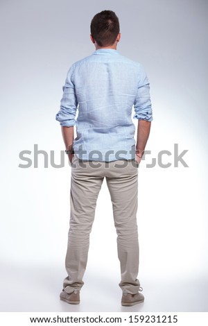 full length back view portrait of a young casual man with both hands in pockets. on gray background - stock photo