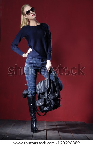 Full length Beautiful fashion casual girl wearing sunglasses with bag standing posing on wooden floor